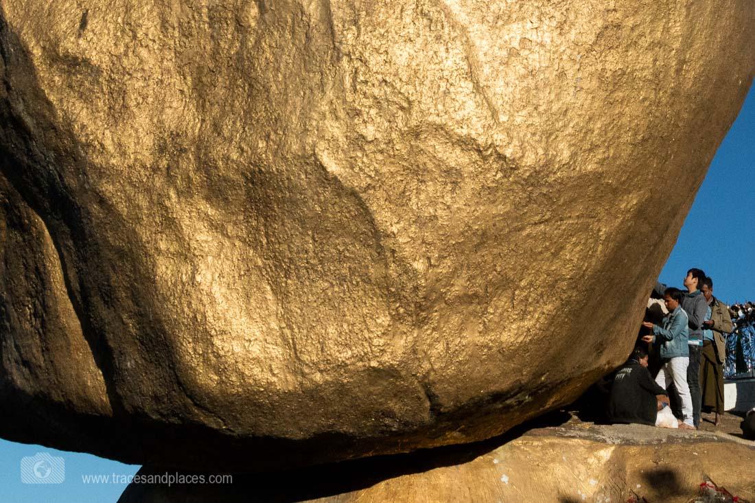 Männer kleben Blattgold an den goldenen Felsen