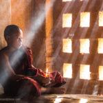 Kleiner Mönch in Tempel mit Lichtstrahlen